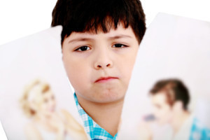 Upset boy standing in front pcture of parents with problems agai